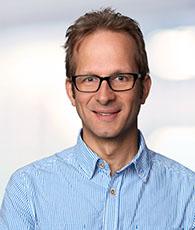 Dirk Flöter, ein Mann mit kurzen dunkelblonden Haaren, Brille und blau kariertem Hemd