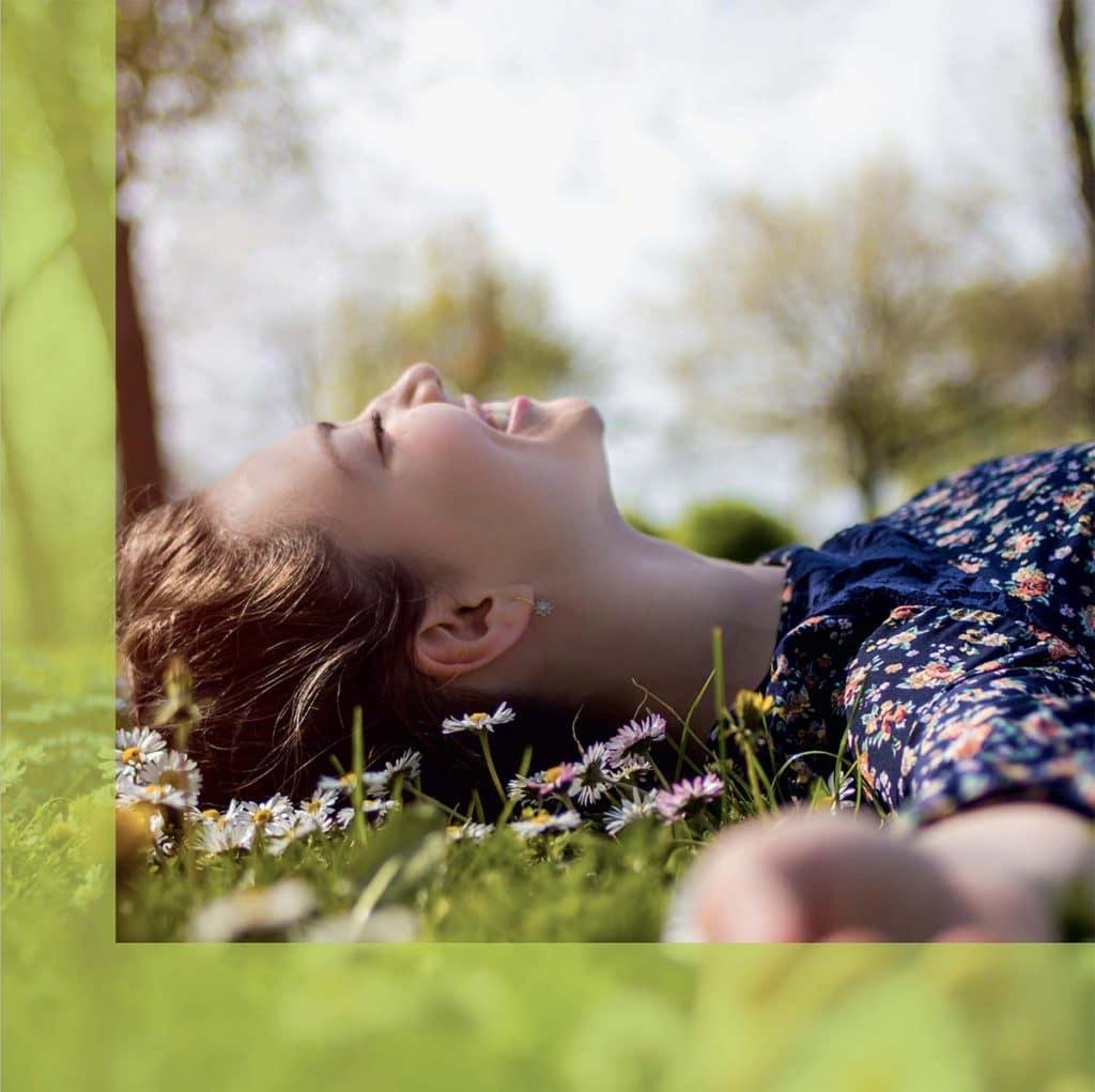 Eine im Grass liegende Frau mit geschlossenen Augen