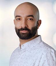 Ashkan Jafari, ein Mann mit schütterem Haar und dunklem Bart im weiß, gemustertem Hemd